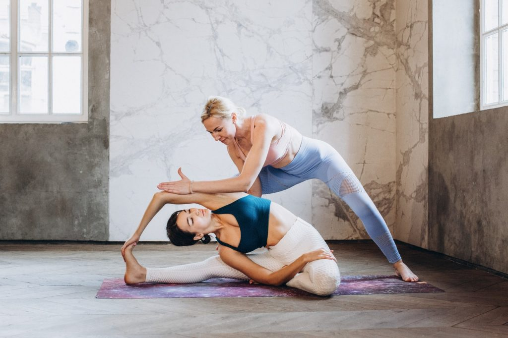 yoga-instructor-helping-a-student-3822194